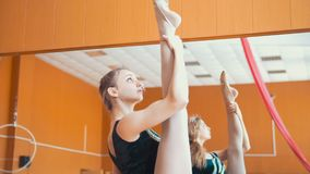 Young athletic woman gymnast doing stretching leg on barre in a studio. Close up Stock Photos