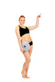Young athletic woman holding balance board and pointing for copyspace or something Stock Photography
