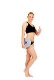Young athletic woman holding balance board and shows thumb up Stock Image