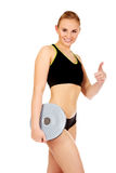 Young athletic woman holding balance board and shows thumb up Royalty Free Stock Photography