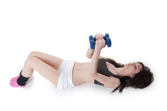 Young athletic woman holding a dumbbells. Young athletic woman wear a black cotton belly top and white shorts lying on back and lifting dumbbells, isolated on Stock Images