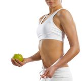 Young athletic woman holding a green apple Royalty Free Stock Images