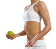 Young athletic woman holding a green apple Royalty Free Stock Image