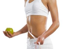 Young athletic woman holding a green apple Royalty Free Stock Photography
