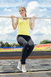 Young athletic woman holding on to horizontal bar Stock Photography