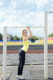Young athletic woman holding on to horizontal bar Royalty Free Stock Images