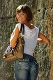 Young, athletic woman in jeans with handbag. Stock Photos