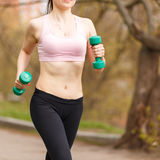 Young athletic woman jogging with dumbbells in park Stock Image