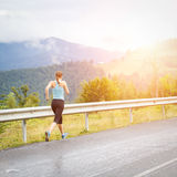Young athletic woman jogging on road in mountains Royalty Free Stock Photos