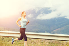 Young athletic woman jogging on road in mountains Royalty Free Stock Photography