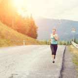 Young athletic woman jogging on road in mountains Royalty Free Stock Images