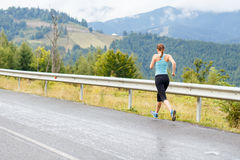 Young athletic woman jogging on road in mountains Stock Images
