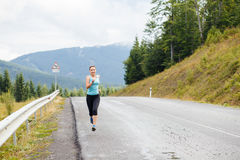 Young athletic woman jogging on road in mountains Stock Photos