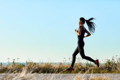 Young athletic woman jogging on rural road in early morning. Sporty girl in black training clothes running toward the sun. Photo with copy space on blue sky Stock Photography