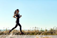 Young athletic woman jogging on rural road in early morning. Sporty girl in black training clothes running toward the sun. Photo with copy space on blue sky Stock Photo