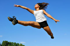 Young athletic woman in a long jump. On blue sky background Stock Photography