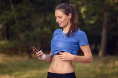 Young athletic woman looking at her mobile. Young athletic woman out training in the woods standing looking at her smart phone as she uses a mobile application Stock Photography