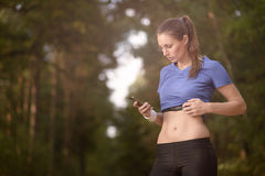 Young athletic woman looking at her mobile. Young athletic woman out training in the woods standing looking at her smart phone as she uses a mobile application Stock Photo