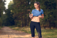 Young athletic woman looking at her mobile. Young athletic woman out training in the woods standing looking at her smart phone as she uses a mobile application Royalty Free Stock Photography