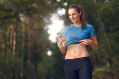 Young athletic woman looking at her mobile. Young athletic woman out training in the woods standing looking at her smart phone as she uses a mobile application Stock Image