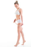 Young athletic woman measuring waist measuring tape, isolated ov Royalty Free Stock Images