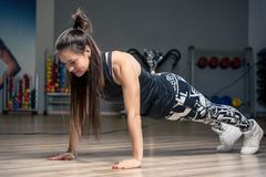 Young athletic woman performing an exercise strap on the floor i. N the gym Stock Images