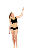 Young athletic woman pointing for copyspace or something.  Royalty Free Stock Photos