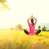 Young athletic woman practicing yoga on a meadow at sunset Stock Photo