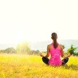 Young athletic woman practicing yoga on a meadow at sunset. Image with lens flare Royalty Free Stock Photos