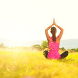 Young athletic woman practicing yoga on a meadow at sunset Royalty Free Stock Images