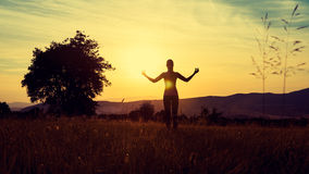 Young athletic woman practicing yoga on a meadow at sunset. Silhouette Stock Images