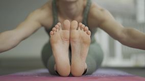 Young athletic woman practicing yoga. Paschimottanasana pose. Front view, foot level stock video footage