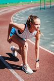 Young athletic woman preparing to run at stadium, outdoors. The concept of healthy lifestyle royalty free stock image