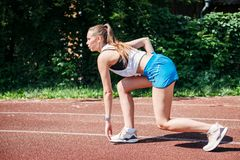 Young athletic woman preparing to run at stadium, outdoors.view from side. concept of healthy lifestyle stock photography