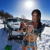 Young athletic woman pulling car in winter. Day Royalty Free Stock Image