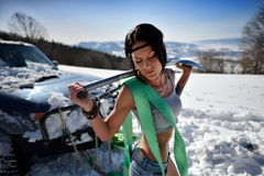 Young athletic woman pulling car in winter Stock Photos