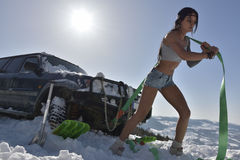 The young athletic woman pulling car in winter. Young athletic woman pulling car in winter Stock Photography