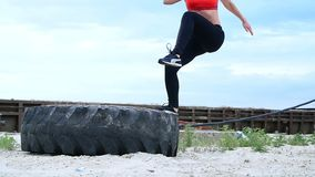 A young athletic woman in a red top and black leggings performs different strength exercises using a large heavy tractor stock footage