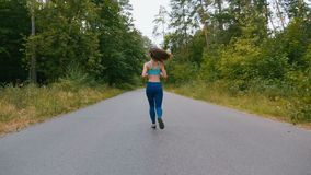 Back view of Young woman runner training in summer park. Fitness girl jogging outdoor. Morning running concept. Young athletic woman runner training in summer stock video