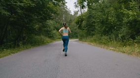 Back view of Young woman runner training in summer park. Fitness girl jogging outdoor. Morning running concept. Young athletic woman runner training in summer stock video footage