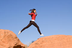 Young athletic woman running. Beautiful young athletic woman running and jumping on red rocks Stock Images
