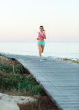 Young athletic woman running along a path by the sea Stock Images