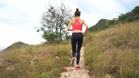 Young athletic woman running on mountain trail. Sunset Workout in Nature. Fit girl in pink top run. stock footage