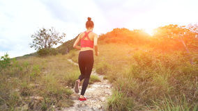 Young athletic woman running on mountain trail. Sunset Workout in Nature. Fit girl in pink top run.