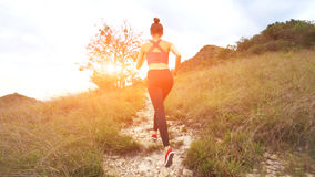 Young athletic woman running on mountain trail. Sunset Workout in Nature. Fit girl in pink top run. 4K Royalty Free Stock Photos