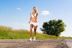 Young athletic woman running on the road Royalty Free Stock Photo