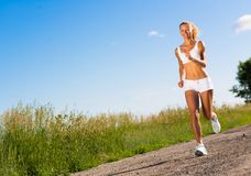 Young athletic woman running on the road Royalty Free Stock Photography