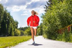 Young athletic woman running on the road Royalty Free Stock Photos