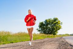 Young athletic woman running on the road. Exercise outdoors Stock Photos