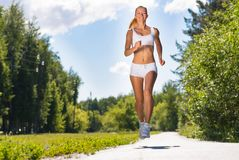 Young athletic woman running on the road Stock Photos